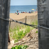 "BRYAN EATON/ Staff Photo. Sunbathers are framed by snow fencing at Salisbury Beach on Tuesday which really was a true ""beach day."""