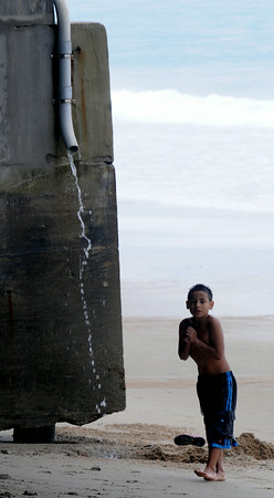 JIM VAIKNORAS/Staff photo A young boy shivers as he washs off him feet with rain water after swimming at a nearly deserted Salisbury Beach on a rainy Fourth of July Morning.