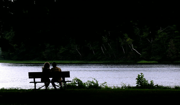 JIM VAIKNORAS/Staff photo A couple sit in Alliance Park along the Merrimack River in Amesbury Monday afternoon.