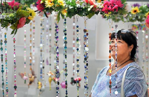 BRYAN EATON/ Staff Photo. Joanne Vien of Merrimac checks out Fairy Bead Sun Catchers made by Rita Scalera of Hampton, N.H. at the Market Square Craft Fair.