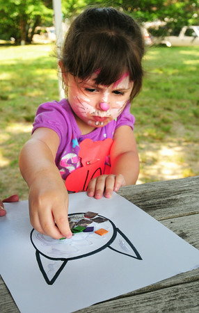 BRYAN EATON/ Staff Photo. Wearing a bunny face painting Lucy Cassidy, 3, of Amesbury fills in a cat mosaic at the craft table at Kids' Day in the Park. She also particpated in the Teddy Bear Parade.