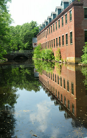 BRYAN EATON/ Staff Photo. This old mill building, now housing condominiums, reflects a still Powow River above the dam in Amesbury's Upper Millyard. Missing from the photo is the scores of ducks who seem to be there constantly.
