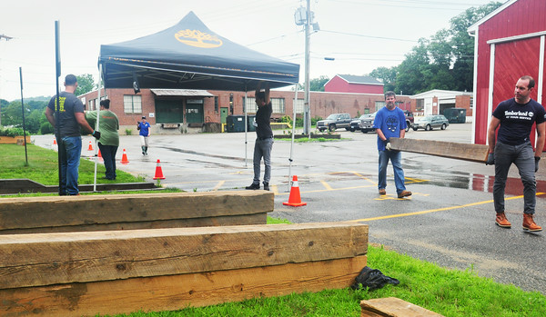 BRYAN EATON/ Staff Photo. Employees of Timberland volunteered for their community service at Coastal Connections in Amesbury on Wednesday. The crew was building a huge raised flower box that will allow people in wheelchairs to tend to the flowers and are going to grow herbs as well.