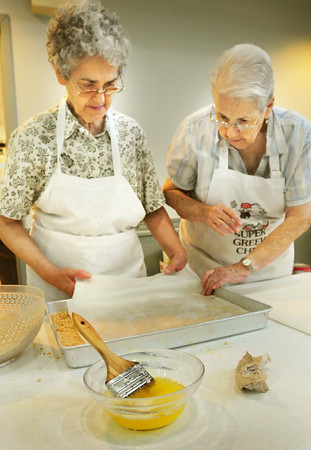 BRYAN EATON/ Staff Photo. Chrysanthe Machiros, left, and Anna Mamakos  lay phyllo dough, which they spread with melted butter, crumbled walnuts and repeat several layers to make baklava.