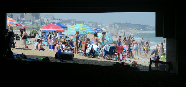 JIM VAIKNORAS/Staff photo  A crowded Salisbury Beach is framed by the floor and supports under the Pavilion on a hot July afternoon Wednesday.