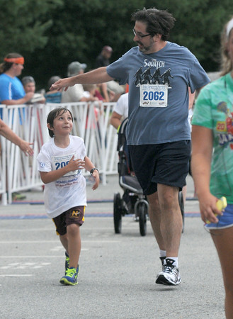 JIM VAIKNORAS/Staff photo  Tom Salemi finishes the Lions Club Yankee Homecoming  5k with his son Theo, who is running his first race.