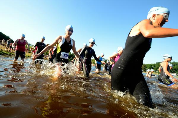 JIM VAIKNORAS/Staff photo Swimmer enter Lake Gardner in Amesbury at the start of the 2014 Dam Triathlon Saturday.