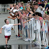 JIM VAIKNORAS/Staff photo Runner Ben St. Lawrence high fives the crowd as he finishes the Lions Club Yankee Homecoming 5k in Newburyport.