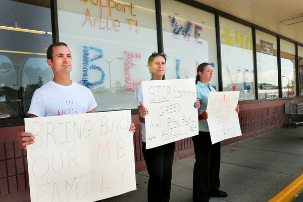 BRYAN EATON/Staff Photo. Off duty Market Basket employees hold signs outside the Newburyport Market Basket, from left, Michael Schwartz, Jacqueline Sollazzo and Candy Fowler. Several customers walking by wished them well and agreed with their message.