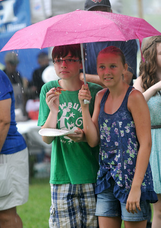 JIM VAIKNORAS/Staff photo Kate Volpone and Charlie Volpone the son and niece of Yankee Homecoming Chiarman Michael Volpone keep dry under an umbrella the rain at Old Fashiioned Sunday on the Mall in Newburyport Sunday.