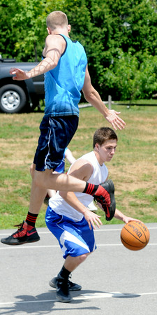 JIM VAIKNORAS/Staff photo Bobby Campbell up fakes Jack Fortin in the TheCarriageTownThrowDown Saturday at Amesbury Park. Proceeds from the 3 on 3 basketball tournament went to the  Amesbury Educational Foundation.