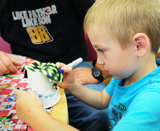 "BRYAN EATON/ Staff Photo. Trevor Comora, 6, uses a magic marker to ""Make a Mad Scientist"" which he called Henry. He was in the Summer Program in the Children's Room at the Amesbury Public Library."