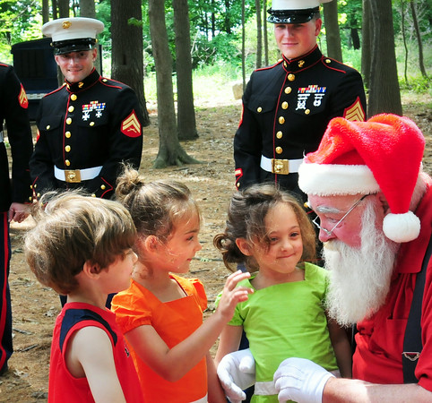 BRYAN EATON/ Staff Photo. Several members of the U. S. Marine Corps were on hand yesterday for the Christmas in July event at Hodgie's Ice Cream in Amesbury where children got a free ice cream sundae for each new toy donated for the Marines' Toys for Tots program. Santa Claus was on hand, wearing shorts in the 90 degree weather, here meeting triplets, Charlie, Maggie and Sophie Himmel, 5, of Amesbury.