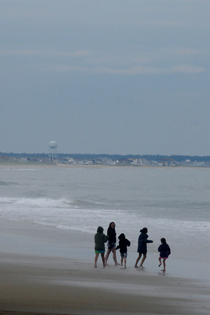 JIM VAIKNORAS/Staff photo  A group of beach goers in sweatshirts enjoy a rainy and empty Salisbury Beach.