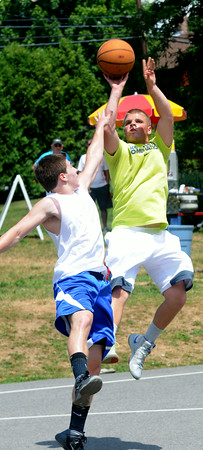 JIM VAIKNORAS/Staff photo Kyle Arseneau shoots over Bobby Campbell in the The CarriageTown ThrowDown saturday at Amesbury Park. Proceeds from the 3 on 3 basketball tournament went to the  Amesbury Educational Foundation.