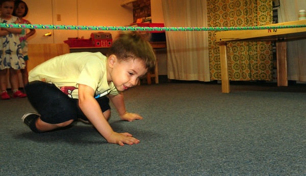 BRYAN EATON/ Staff Photo. Gabriel Simiao, 4, of Newburyport goes under the limbo line at the Newburyport Montessori School on Thursday. They were doing Olympic events for their summer program.