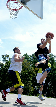 JIM VAIKNORAS/Staff photo Matt Talbot looks to pass around Curran O'Connor in the TheCarriageTownThrowDown Saturday at Amesbury Park. Proceeds from the 3 on 3 basketball tournament went to the  Amesbury Educational Foundation.