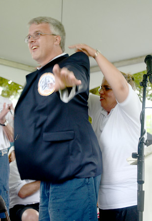 JIM VAIKNORAS/Staff photo Yankee Homecoming Chiarman Michael Volpone get his jacket from last years chairman Tammy Jennings at Old Fashioned Sunday on the Mall in Newburyport Sunday.