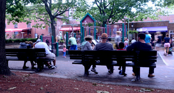 JIM VAIKNORAS/Staff photo People enjoy ice cream and shade as they watch their kids play at the Tot Lot on Inn Street in Newburyport.