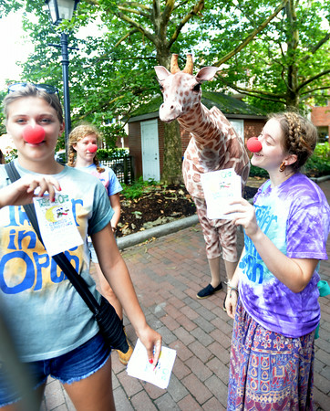 BRYAN EATON/ Staff Photo. A giraffe spotted on the Newburyport Waterfront was thought to be the Market Basket supporters' mascot, but was actually with these members of Theater in the Open. They were passing out flyers for their upcoming fundraising Circus Smirkus shows.