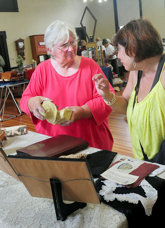 BRYAN EATON/ Staff Photo. Peggy Mears, left, of Kingston, NH, originally from Newburyport, shows the bust of a fisherman to Penny Lazaruz, Newburyport, who bought the piece at the 50th Annual Antique Show and Sale.