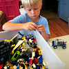 BRYAN EATON/Staff Photo. Lachy Rosolowski, 7, chooses Lego pieces to go with his robotic car at the Kelley School Youth Center. He and others were creating different contraptions with the help of Kevin Husson, in one of the programs by Newburyport Youth Services during school vacation.