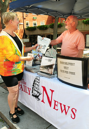 """BRYAN EATON/Staff Photo. Daily News employee David Labovitz hands Patty King of Newburyport a complimentary copy of the paper at the company booth on Inn Street before she checks out the company's new book """"Newburyport 250th."""""""