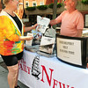 "BRYAN EATON/Staff Photo. Daily News employee David Labovitz hands Patty King of Newburyport a complimentary copy of the paper at the company booth on Inn Street before she checks out the company's new book ""Newburyport 250th."""