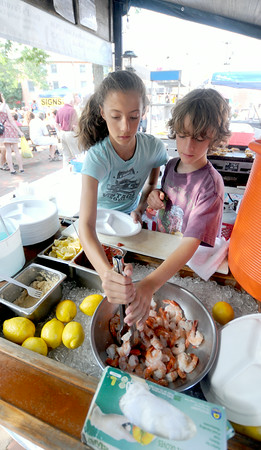 JIM VAIKNORAS/Staff photo  Madeline Pfingst and Will Marshal serve shrimp at David's Tavern Lobster Cakes Booth in Market Square in Newburyport. The pair are the daughter and nephew of owner Steve Pfingst.