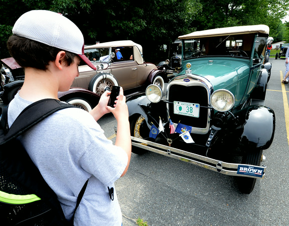 JIM VAIKNORAS/Staff photo Jacod Marshall of Newburyport take a photo with his phone of a 1938 Ford at the Amesbury antique car show on Chestnut Street in Amesbury Saturday.
