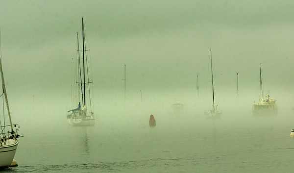 BRYAN EATON/ Staff Photo. Mist from the humidity hangs over the Merrimack River yesterday afternoon hiding some boats with just the masts appearing. The weather is forecast to get brighter and drier into the weekend.