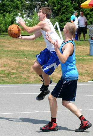 JIM VAIKNORAS/Staff photo  Bobby Campbell drives by Jack Fortin in the TheCarriageTownThrowDown saturday at Amesbury Park. Proceeds from the 3 on 3 basketball tournament went to the  Amesbury Educational Foundation.