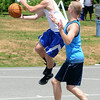 JIM VAIKNORAS/Staff photo  Bobby Campbell drives by Jack Fortin in the The CarriageTown ThrowDown saturday at Amesbury Park. Proceeds from the 3 on 3 basketball tournament went to the  Amesbury Educational Foundation.