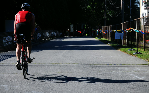 JIM VAIKNORAS/Staff photo  A cyclist heads out from Lake Gardner in Amesbury in the Dam Triathlon Saturday.