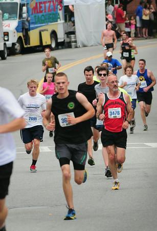BRYAN EATON/Staff Photo. Runners in the 3-mile race run down Merrimac Street at the bottom of Green Street.
