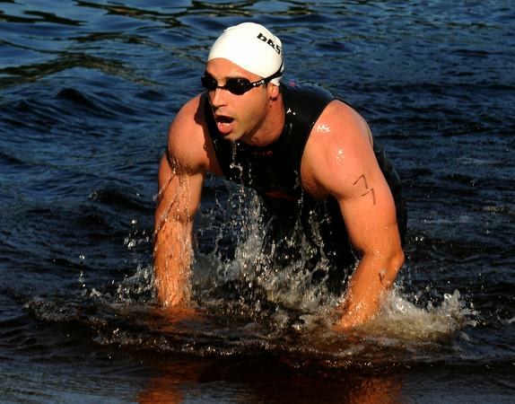 JIM VAIKNORAS/Staff photo #77 emerges from Lake Gardner in Amesbury in the 2014 Dam Triathlon Saturday.