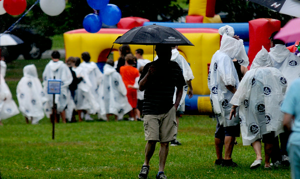 JIM VAIKNORAS/Staff photo A few souls brave the rain at Old Fashiioned Sunday on the Mall in Newburyport Sunday.