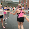 BRYAN EATON/Staff Photo. Volunteers hand out water to runners on Water Street last night.
