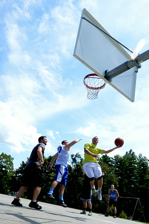 JIM VAIKNORAS/Staff photo Kyle Arseneau sglides in for 2 during TheCarriageTownThrowDown Saturday at Amesbury Park. Proceeds from the 3 on 3 basketball tournament went to the  Amesbury Educational Foundation.