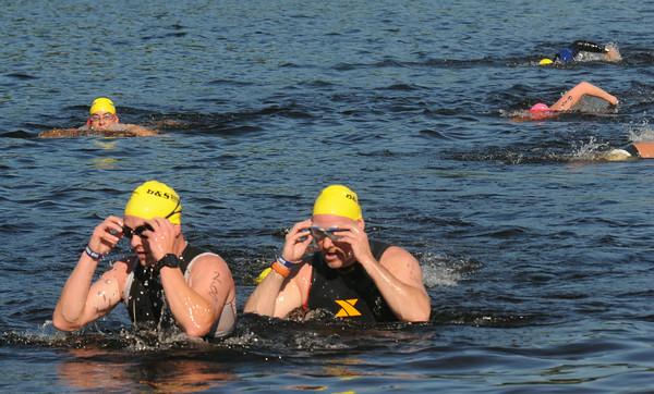 JIM VAIKNORAS/Staff photo Swimmer emerge from Lake Gardner in Amesbury in the 2014 Dam Triathlon Saturday.