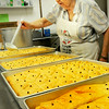BRYAN EATON/ Staff Photo. Anna Mamakos drizzles a honey mixture over the baked baklava on sale at the Greek Festival this weekend.