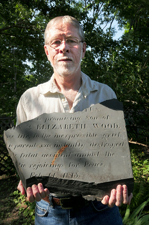 BRYAN EATON/Staff Photo. Mike Prendergast unearthed part of a gravestone in his Newburyport backyard that relates to the death of a 9-year-old in 1815.