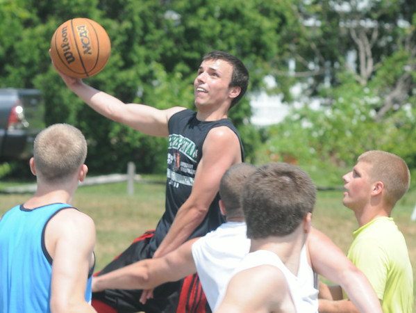 JIM VAIKNORAS/Staff photo Craig Bowen drive to the hoop in the TheCarriageTownThrowDown Saturday at Amesbury Park. Proceeds from the 3 on 3 basketball tournament went to the