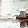 JIM VAIKNORAS/Staff photo Workers transport a portable toilet along the Merrimack River from the Whittier Bridge work site to the staging area in Newburyport Tuesday afternoon.