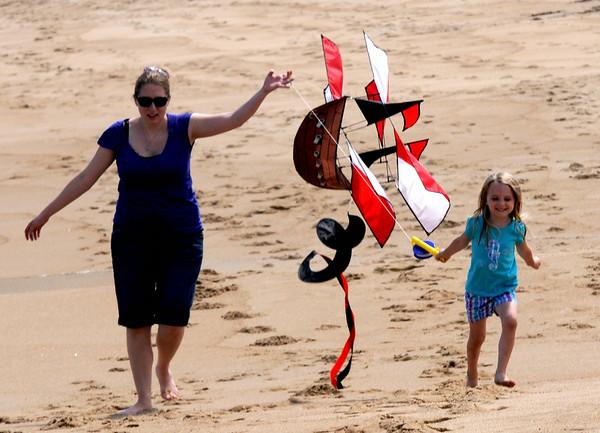 JIM VAIKNORAS/Staff photo Madeline Mazerall, 4, and her mom Megan fly a pirate ship themed kite on Plum Island beach in Newbury Thursday.