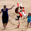 JIM VAIKNORAS/Staff photo Madeline Mazerall, 4, and her mom Megan fly a pirate ship themed kite on Plum Island beach in Newbury Thursday.