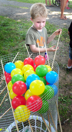 BRYAN EATON/ Staff Photo. Dane Hale, 6, of Amesbury carefully removes sticks trying to not let plastic balls fall in a game of Kerplunk. He was Amesbury Days Kids' Day in the Park.