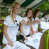 JIM VAIKNORAS/Staff photo Volunteers Annika Jahn, Peyton Baily, and Claudia Curry hand out shirts at Newburyport High for the Lions Club Yankee Homecoming Road Race.