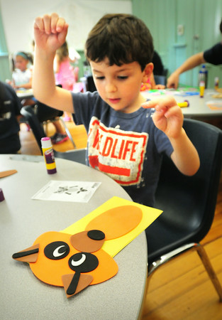 "BRYAN EATON/ Staff Photo. Noah Tarkan, 5, lifts his hands as he completes hit cutout of a raccoon at the Kelley School Youth Center in Newbury on Tuesday morning. He was in the Department of Youth Services program Little Aces where the theme this week is ""Muppets and Puppets."""