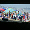 JIM VAIKNORAS/Staff photo  A crowded Salisbury Beach is framed by the floor and supports under the Pavilion on a hot July afternoon.